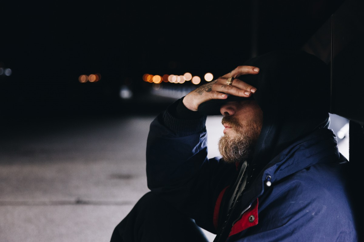 Bearded homeless man holding his head